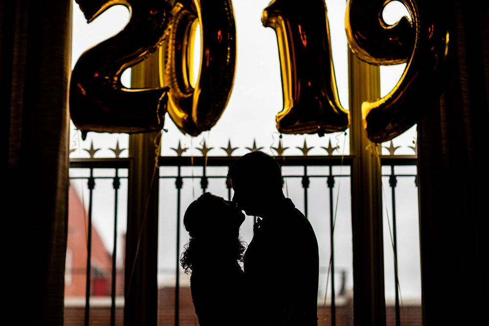 kissing in front of the 2019 balloons on their NYE Wedding - Pearl Weddings & Events
