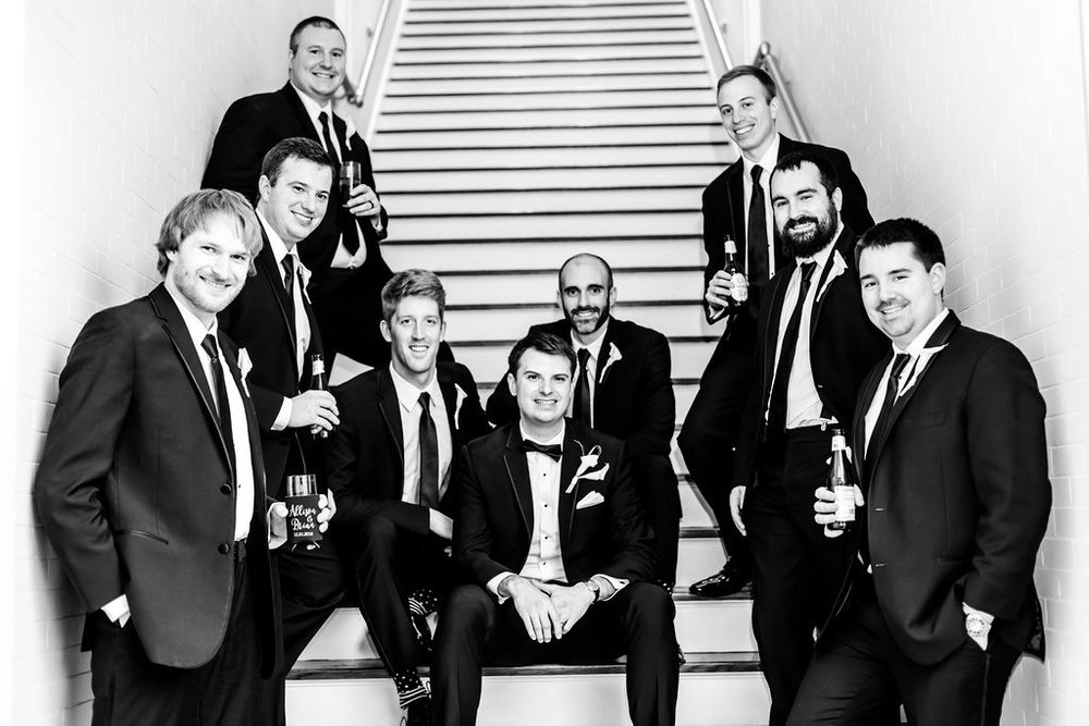 groomsmen posing in the stairwell for an epic wedding photo - Pearl Weddings & Events