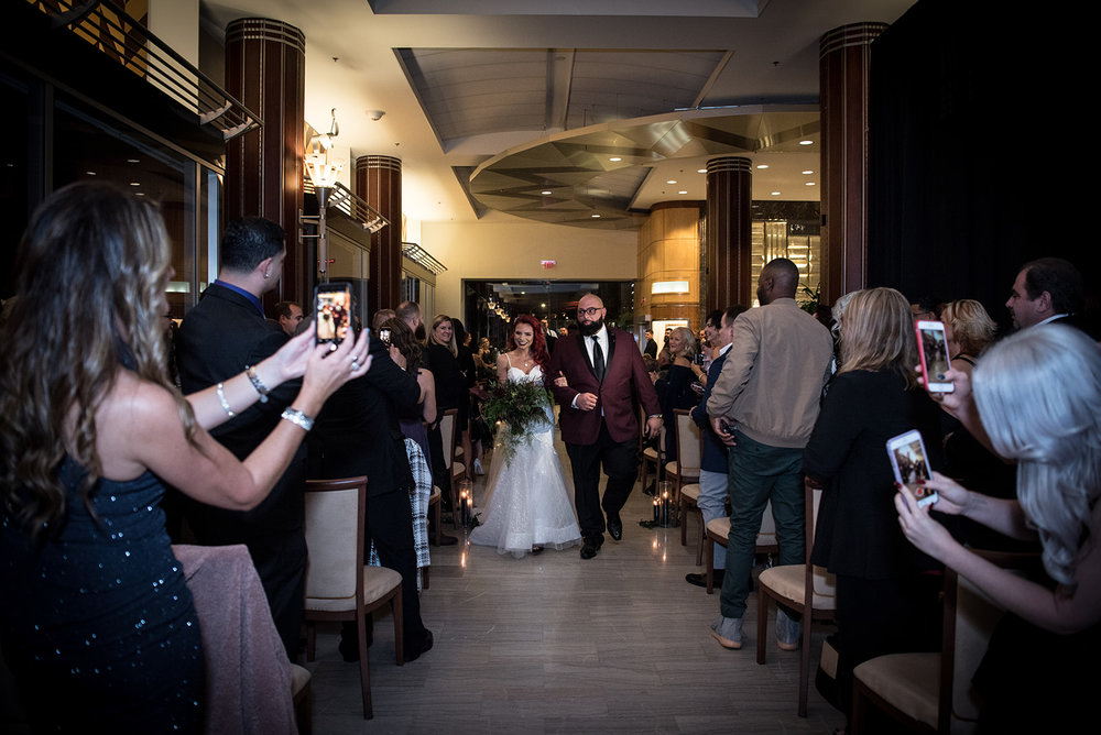husband and wife walking down the aisle together after they were just married - Pearl Weddings & Events