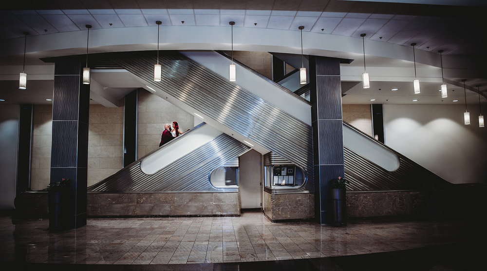 Bride and Groom on stairs and escalator in Hartford for their couples photos - Pearl Weddings & Events