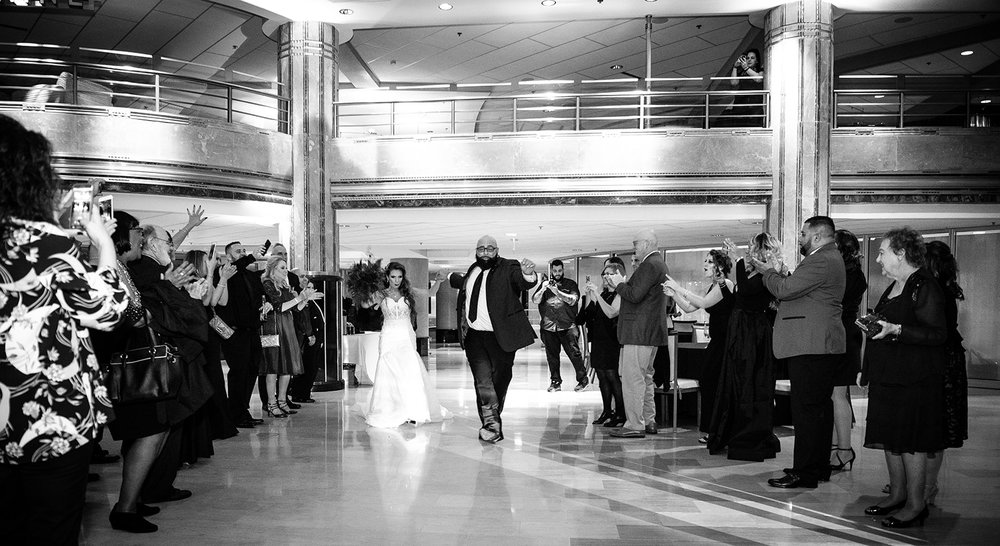 bride and groom entrance down an aisle of their guests - Pearl Weddings & Events