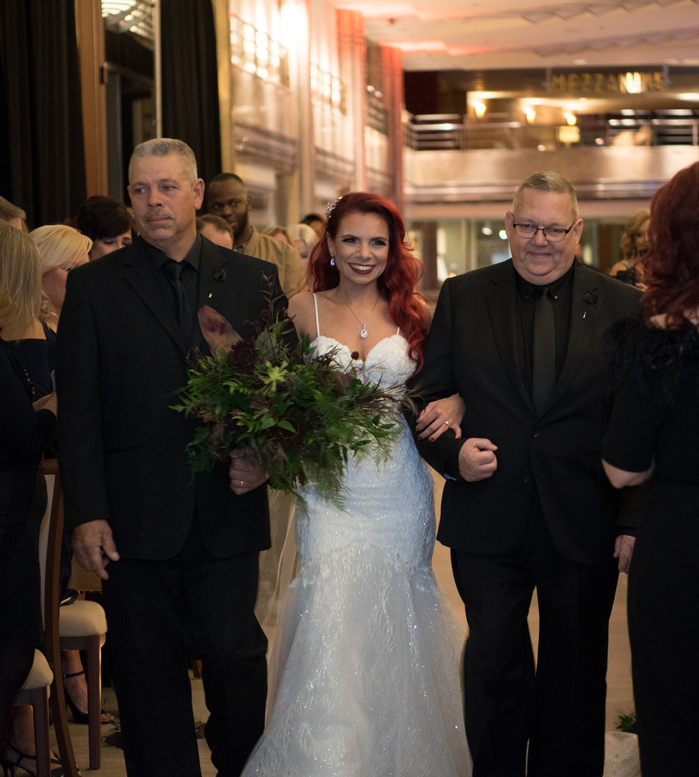 bride being escorted down the aisle by both her dads. She is wearing her Call Blanche dress, Louboutin shoes, a veil, red hair and hair piece - Pearl Weddings & Events