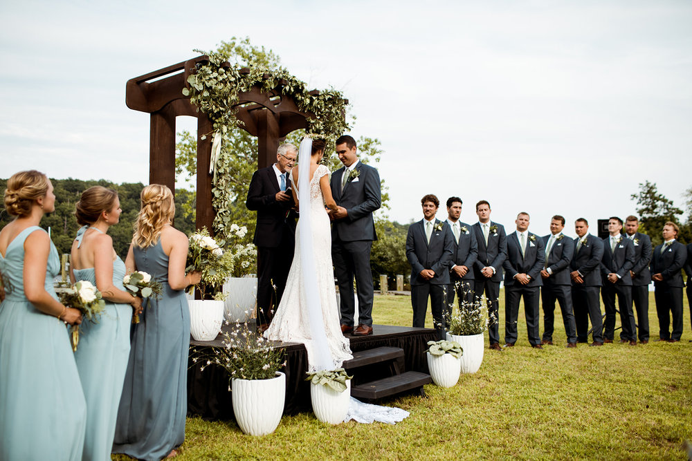 Sommar & Ben's wedding by the water in Connecticut. Wooden wedding arch way and white potted plants for the ceremony decor. - Pearl Weddings & Events