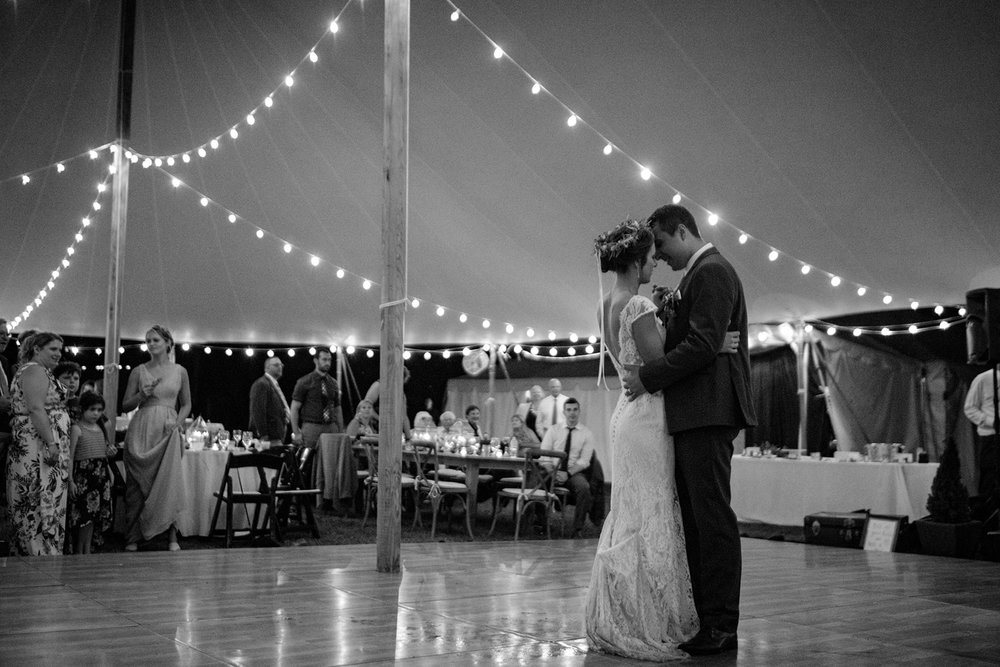 first dance under a sperry tent with cafe lighting strung and a wooden dance floor - Pearl Weddings & Events