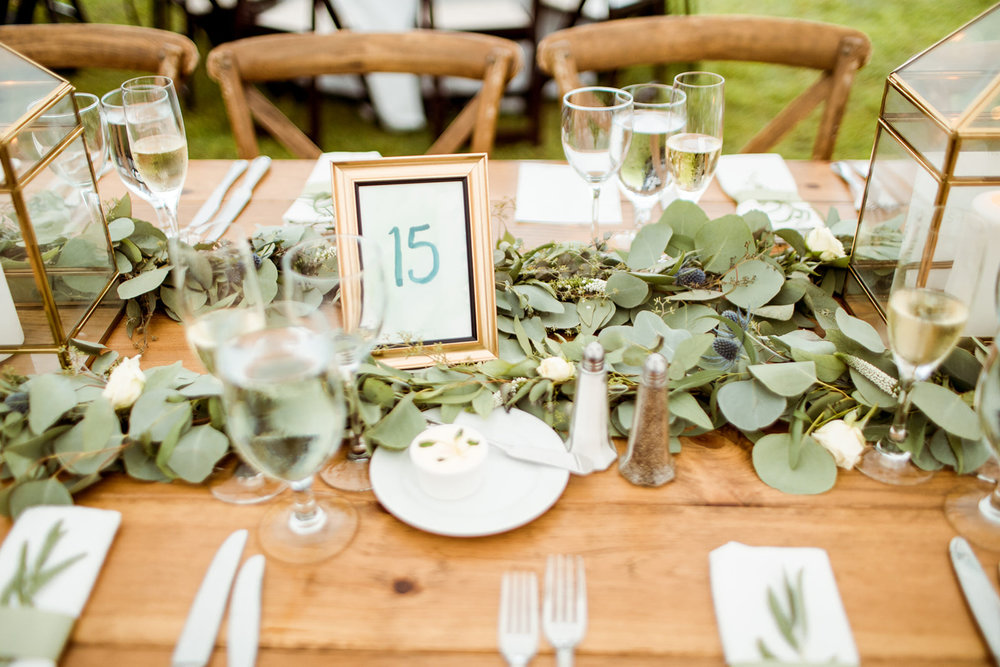 Lush greenery down the middle of the farm tables with framed table numbers and gold lanterns - Pearl Weddings & Events