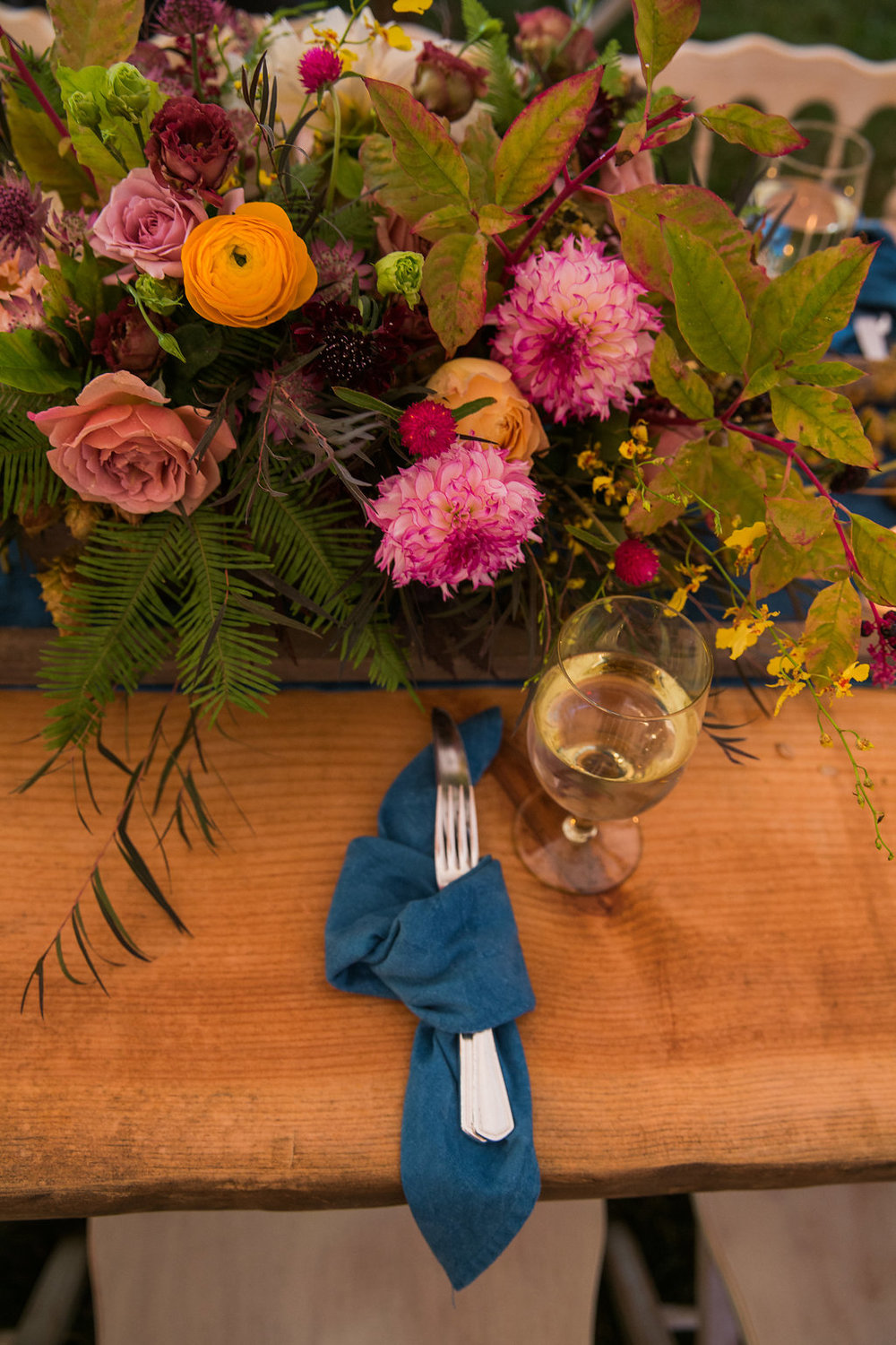 knot denim napkins for your place settings on a farm table with lush center pieces - Pearl Weddings & Events