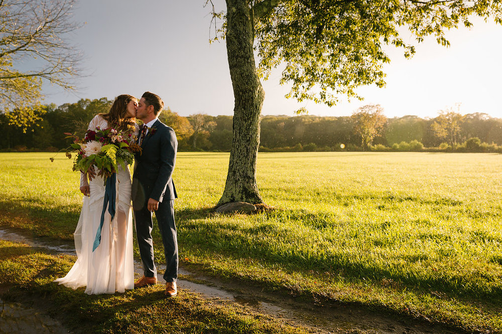 bride dressed in a beautiful Rue De Seine wedding dress and groom with a hop boutonnière at their outdoor farm wedding - Pearl Weddings & Events