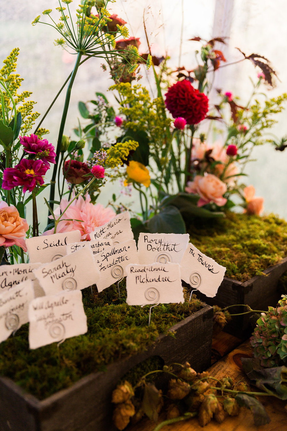 Unique name card display with greenery and organic florals! - Pearl Weddings & Events