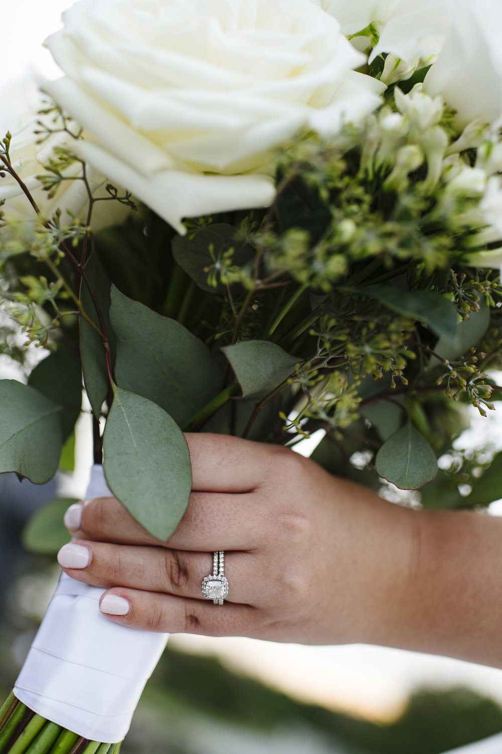 White roses and greenery bouquet with white ribbon tie and exposed stems. Beautiful halo ring photo with engagement ring. - Pearl Weddings & Event