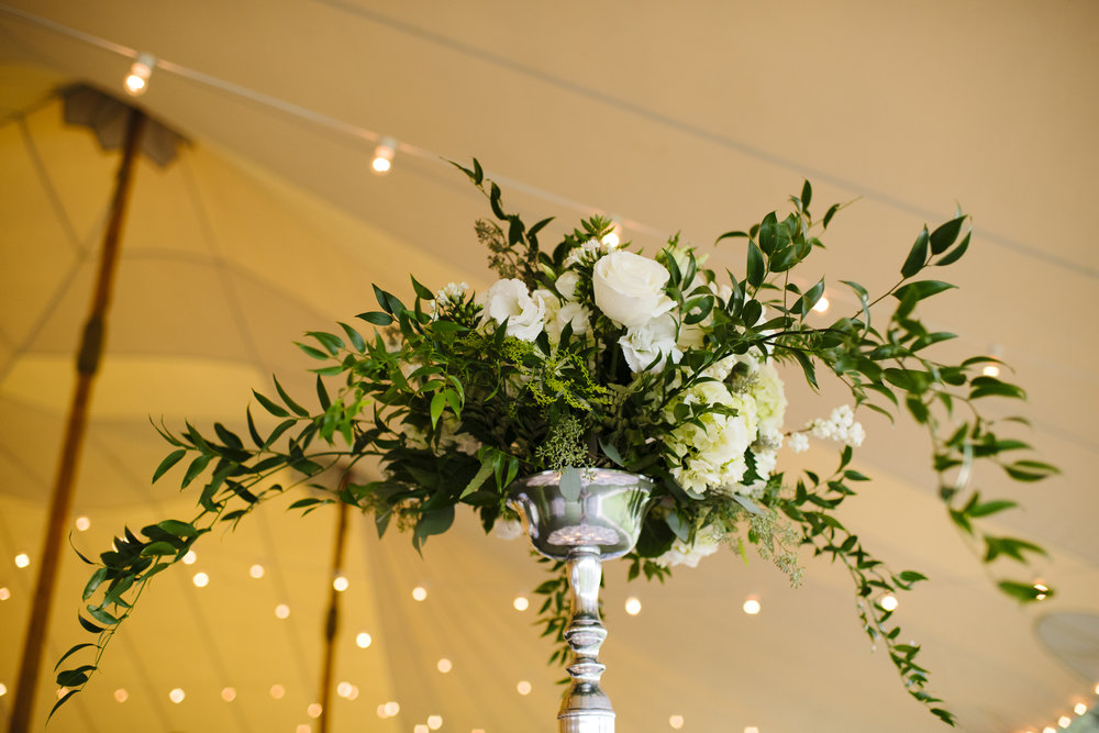 Tall white rose and greenery elegant but classy centerpieces under tent at Jonathan Edwards Winery in Connecticut - Pearl Weddings & Event