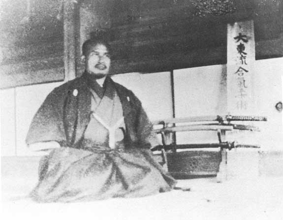 "Morihei Ueshiba in front of a placard reading ""Daito-ryu Aiki-jujutsu."" —  Read More at Aikido Sangenkai"