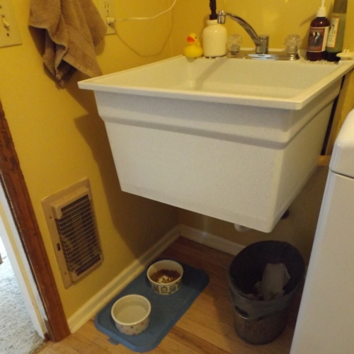 BEFORE: The ugly laundry tub wasn't properly attached to the wall and an outdated energy-hog wall heating unit was slated for removal.