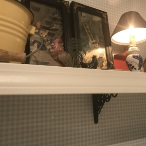 AFTER: In a nod to the house's Dutch Colonial roots, the shelf brackets from  House of Antique Hardware  are a Pennsylvania Dutch reproduction. Clothespins are in the little yellow enamel bucket. The shelf is a fun place to display chicken-y items and antique household toys.