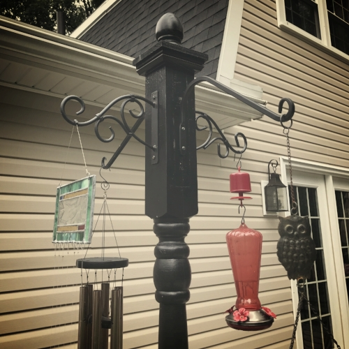 A repurposed porch post takes the place of four shepard hooks in the garden.