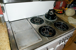The griddle, broiler and burners of a vintage Chambers stove model B, as well as the folding cover.