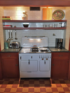 Restored Vintage Chambers stove model 90C highback set in a vintage kitchen with subway tiles and cork floor.