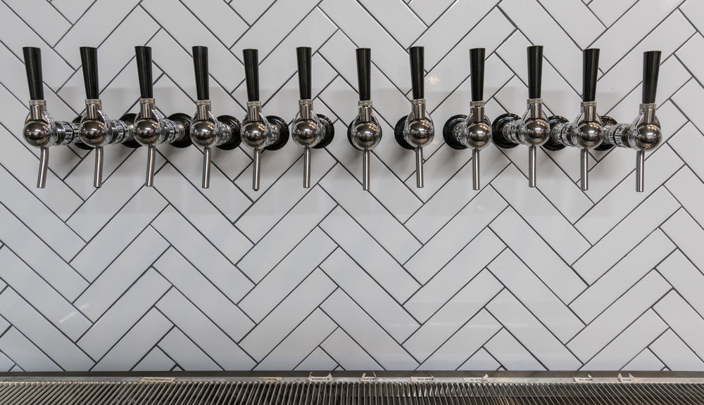 Beer Taps on a White Tile Background