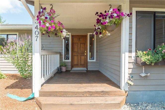 Cheerful and sheltered front porch entrance into open living and dining space.