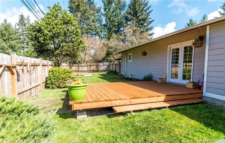 Beautiful fully fenced backyard complete with deck, raised beds, and a garden shed.