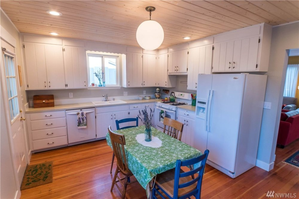 Large, eat-in kitchen features ample storage, knotty pine ceilings, and backdoor out to the deck. Closet, half-bath, and pantry adjoin kitchen.