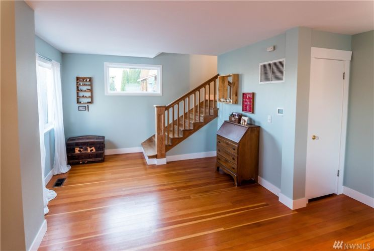 Open staircase (lovingly relieved of layers of dark paint) leads the way to upstairs bedrooms and bath.