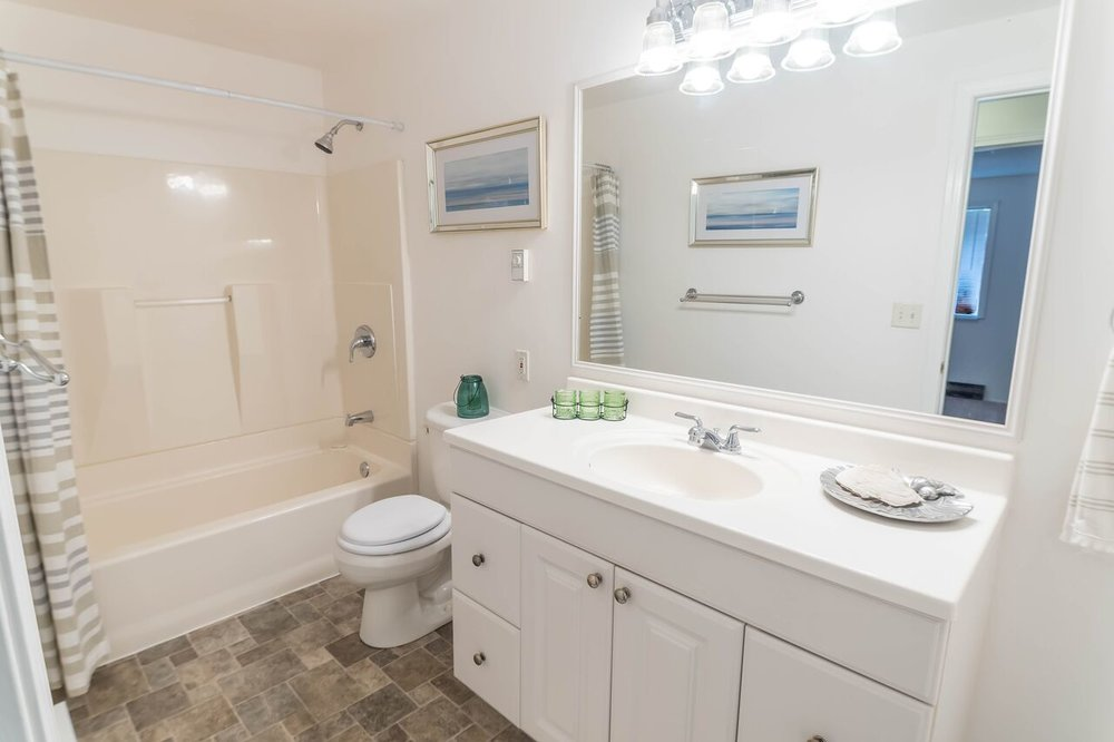 Bright full bath with spacious vanity and easy to clean surface floor and tub-surround.