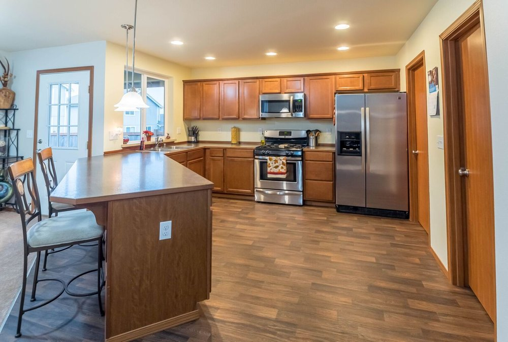 Spacious, open-concept kitchen features bar counter, laminate floors, stainless steel appliances, pantry, and double-sink. Also connects to laundry room which leads into the garage.