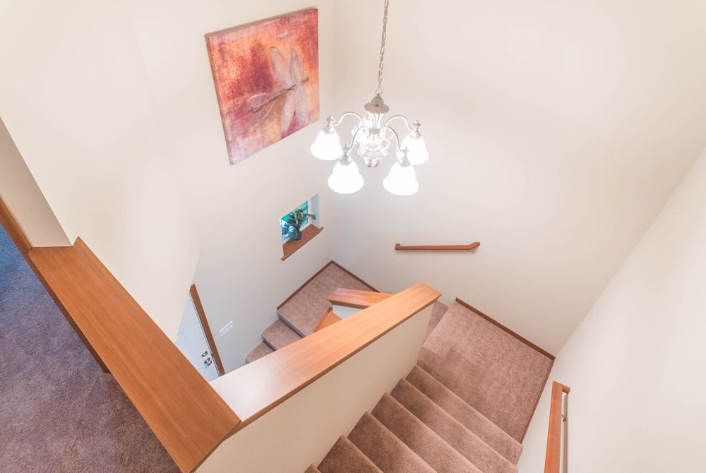 Open staircase lit by chandelier leads from front entrance to upstairs landing, bedrooms, and bathrooms.
