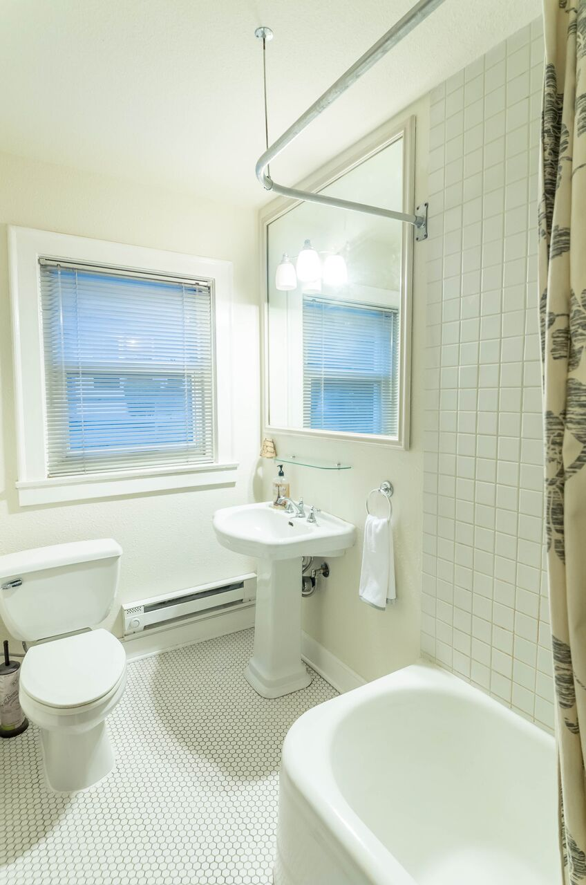 Full bath includes window, pedestal sink, bath/shower, and tile floor.