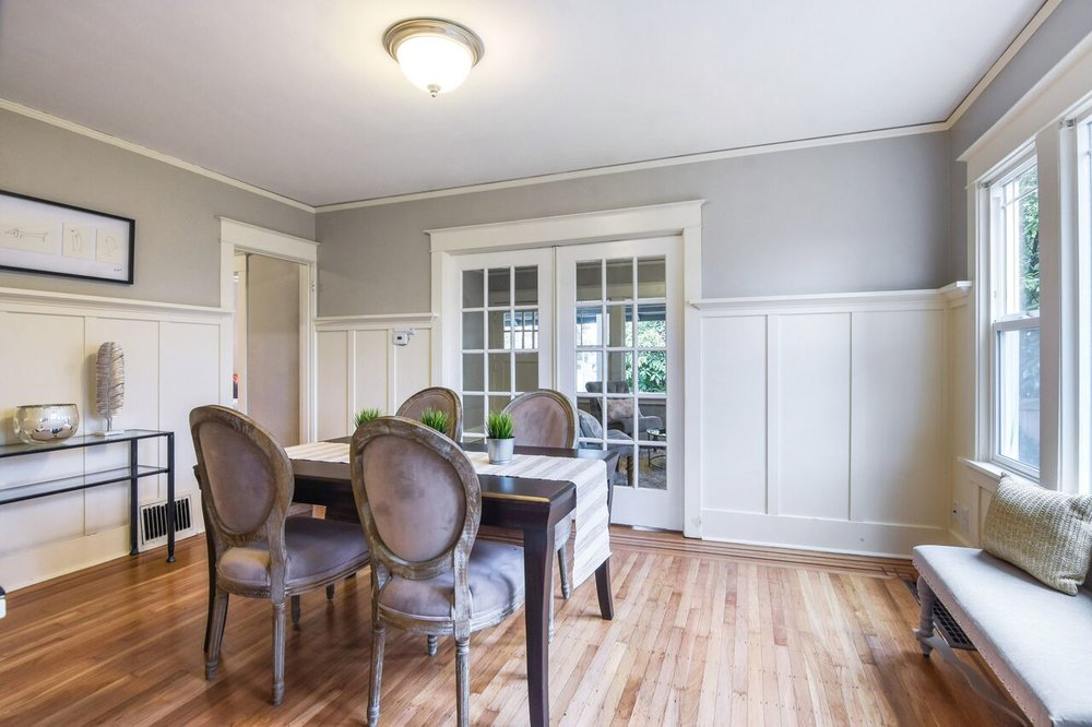 Dining room with sliding glass pocket doors, big windows, and custom hardwood floors. Look close for the colorful hardwoods inlaid around the edges of this room.