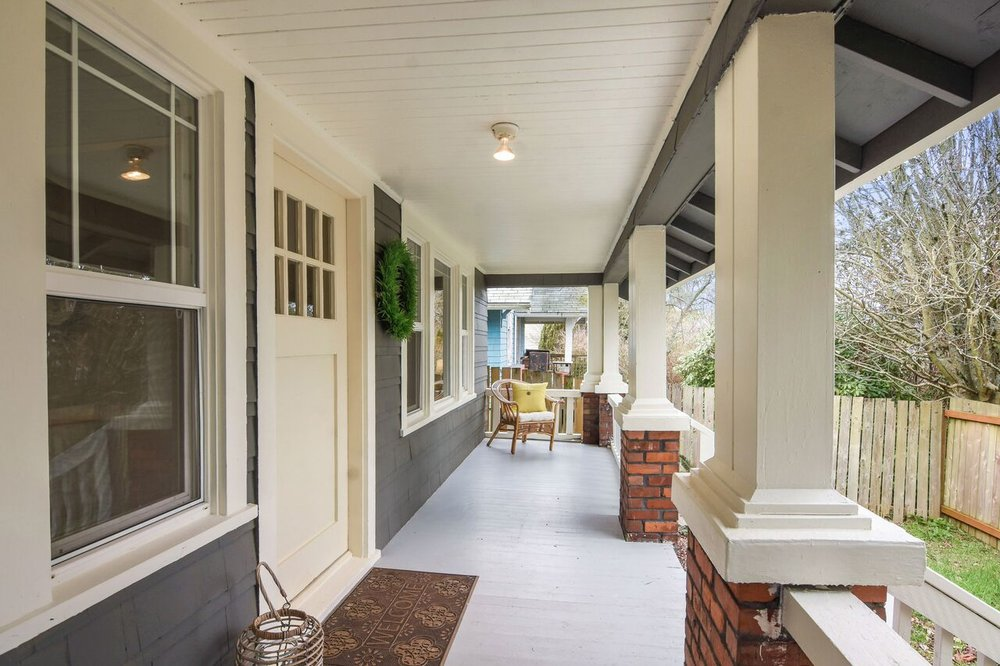 Bungalow style front porch with plenty of room for benches and chairs. A great place to shake off the raincoat before heading in.