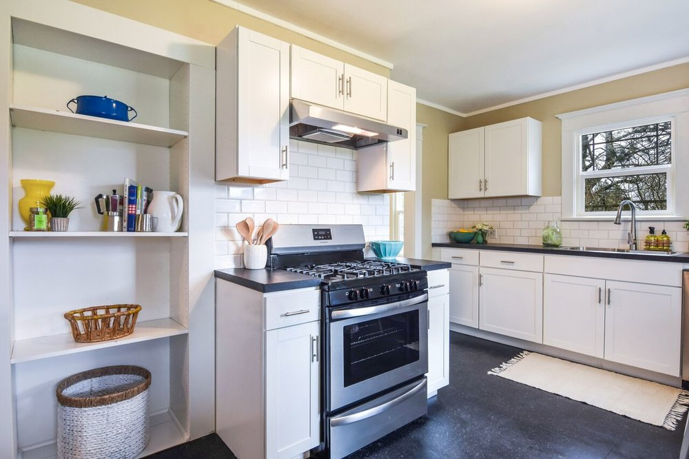 Thoughtfully updated kitchen offers new gas cook stove, new dishwasher and sink, as well as open shelves for storage and display. White subway tile and cabinets contrast nicely with dark vinyl floor.