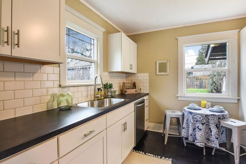 Both bright and practical, this updated kitchen adjoins the dining room and offers access to the backyard as well. New dishwasher and new sink are featured in this photo with a western view out the back window.