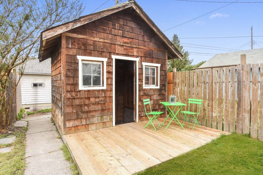 Backyard storage shed cute with shingles and little windows has its own mini patio. It's also a great spot to store the lawnmower and rake.