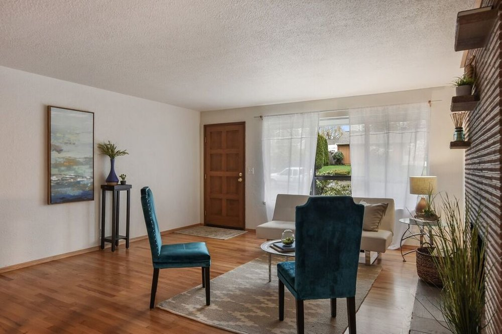 Original mid-century floors and fireplace bring warmth and charm to the front room.