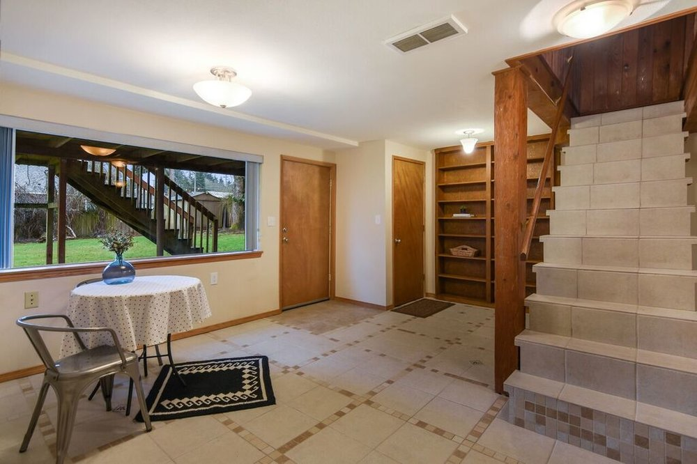 Wide window brings light to the daylight basement, while wooden shelves and trim warm up the space. Separate entrance from the fenced backyard.
