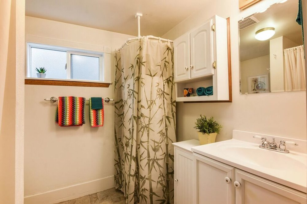 3/4 bath with shower accessed from the laundry room adjacent to the kitchen. Water heater is behind the bamboo curtain.