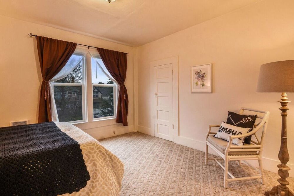 One of two second floor bedrooms with tall windows and carpeted floor.