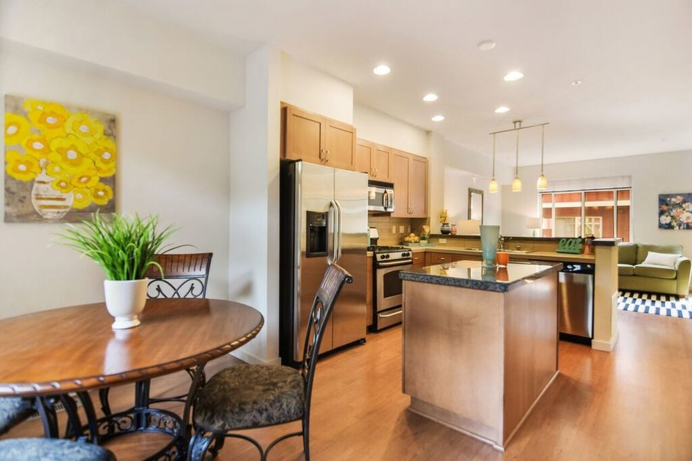 The kitchen features stainless appliances, gas stove, granite countertops, island and bar counter.