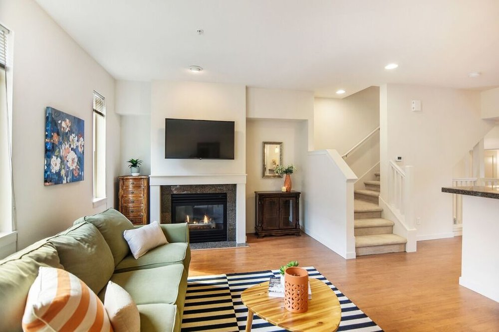 The gas fireplace is ready to keep you cozy in the living room with its  tall ceilings.