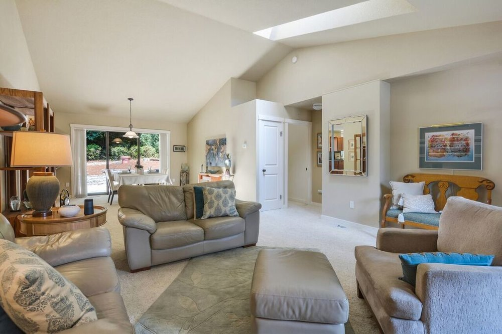 The vaulted ceiling provides a spacious feeling to this open floor plan, and the skylight keeps the room bright with natural light. Notice the coat closet under the skylight.