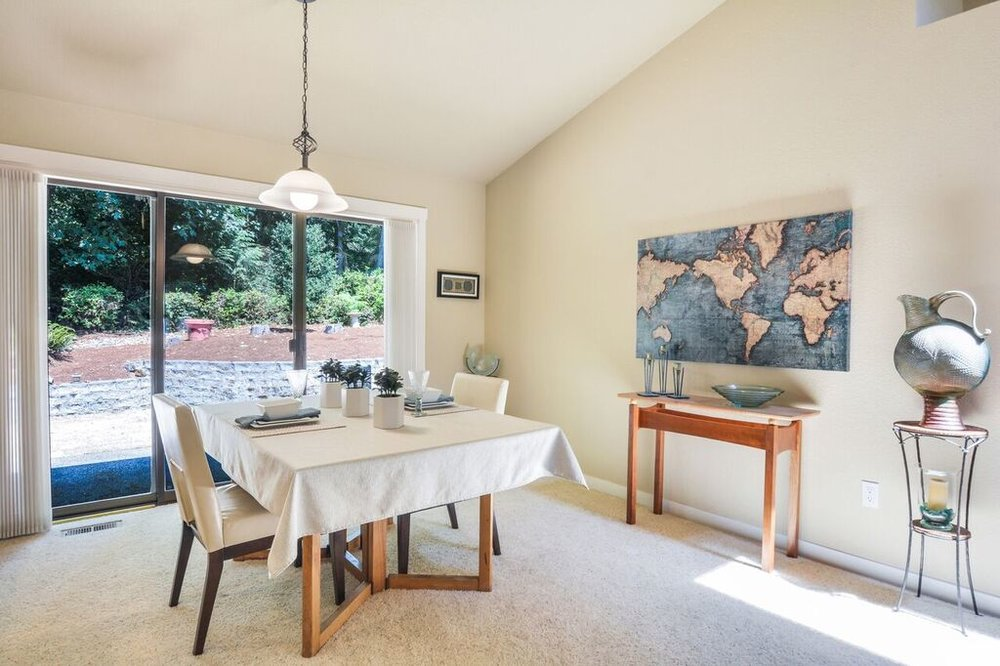 The dining room beneath the vaulted ceiling is bright and open to the kitchen. The triple panel sliding glass door leads to the patio and back yard.