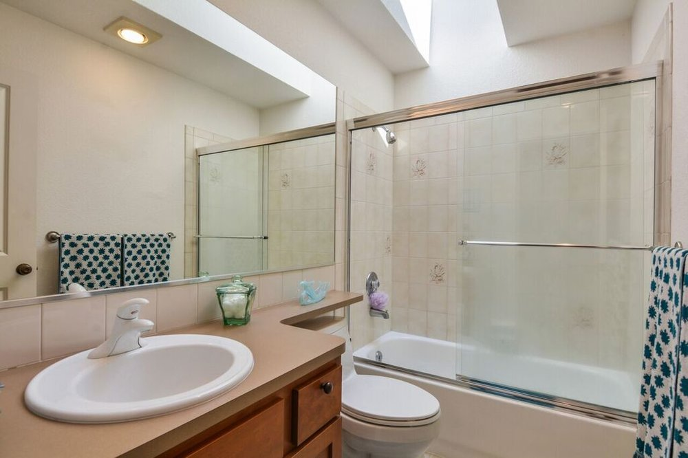 This full bath is accessible from the living room and is next door to the second bedroom. A skylight brings in natural light and the large mirror helps keep things bright.