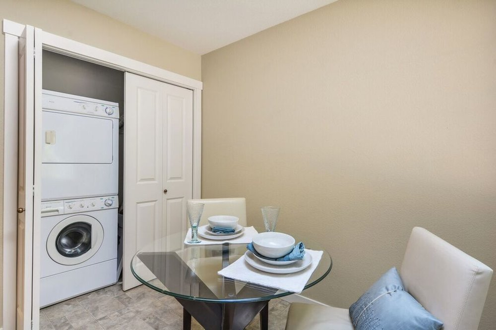 Stacked washer and dryer conveniently located off the kitchen with pantry shelves behind the other door.