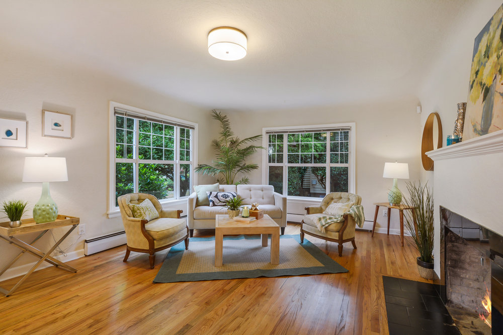 Oak floors, big updated windows, and a fireplace make a cozy living room.