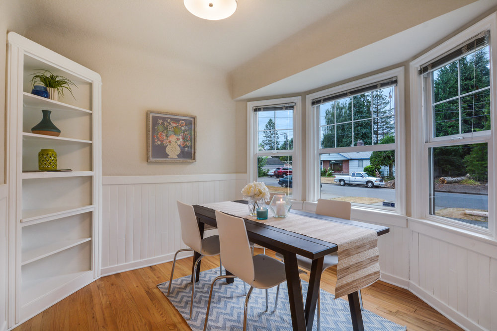 The dining room is located just to the right as you enter the front door. Bay windows, built-in corner shelf, oak floor, and wainscot create a very pretty room.