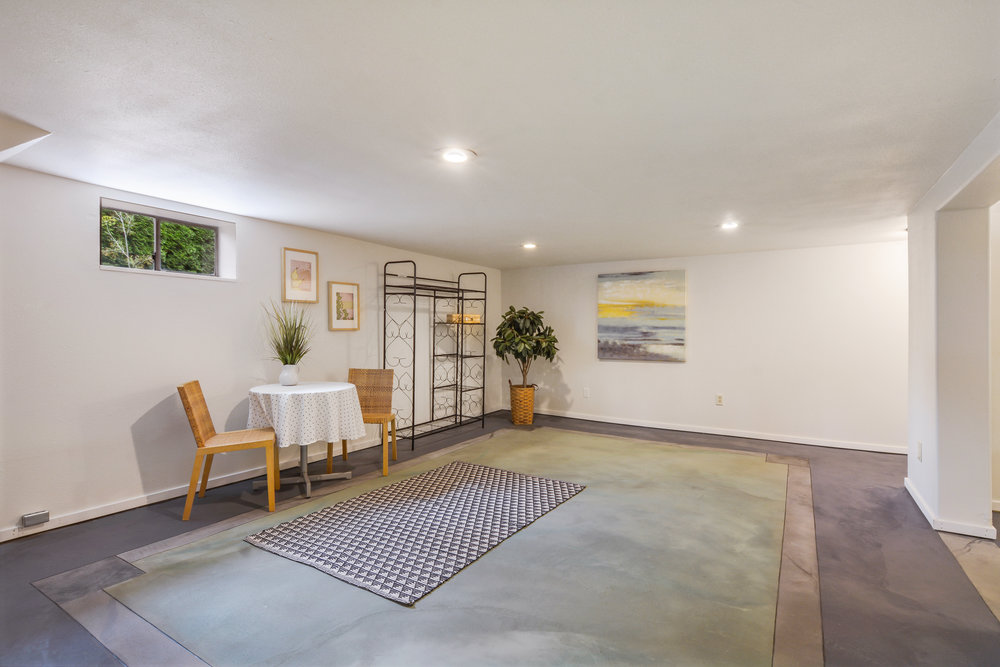 Down the stairs from the kitchen find the finished basement with its artistic concrete floors that bring color and texture to the rooms. This room could be a family room, exercise room, play space or anything needed.