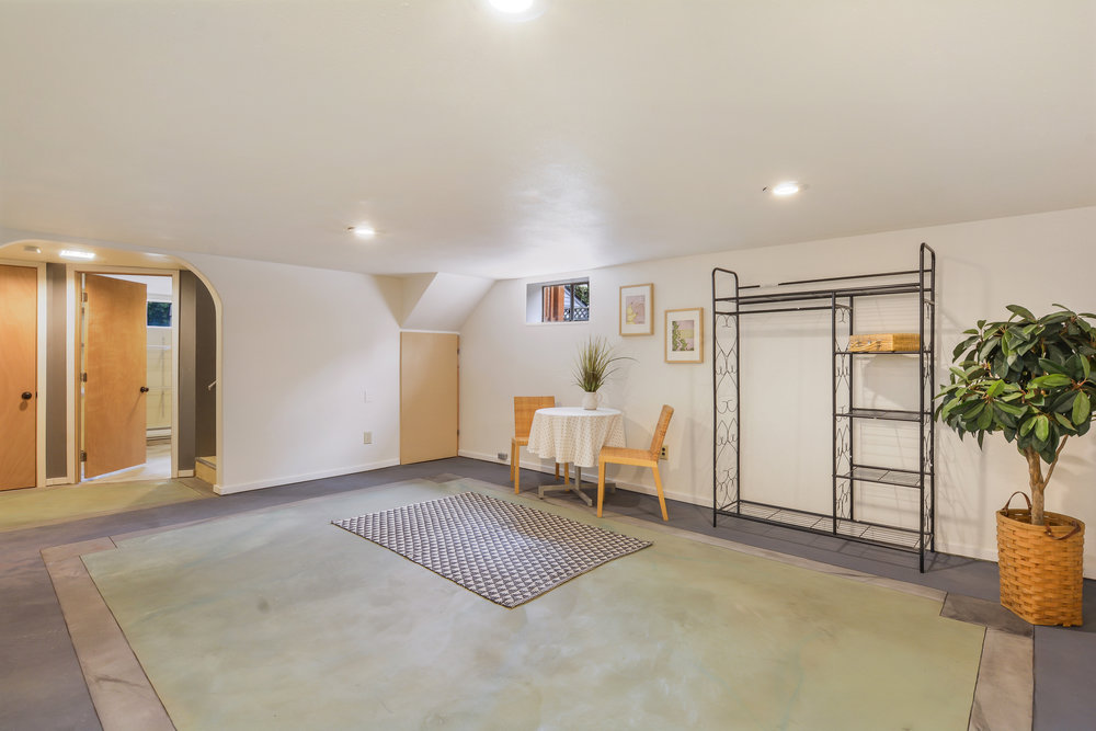 Another view of the large basement room with its arched opening where you see doors to the storage room and laundry/bathroom. There's space for so much in here!