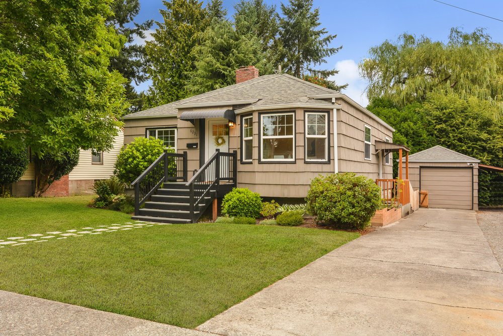 6231 S Bell St - the home faces west. A well maintained lawn, shrubs, magnolia tree, paving stone pathway, and tidy driveway welcome you to this home sided in cedar shakes.