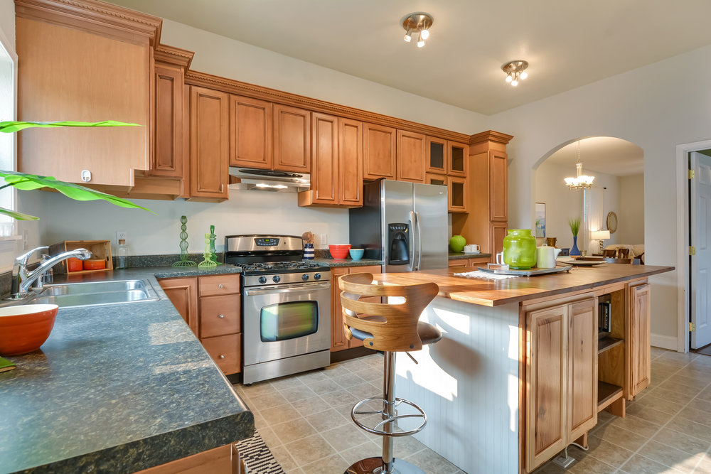 Ample cabinets, stainless appliances, gas stove, and vinyl floors make a practical and attractive kitchen.